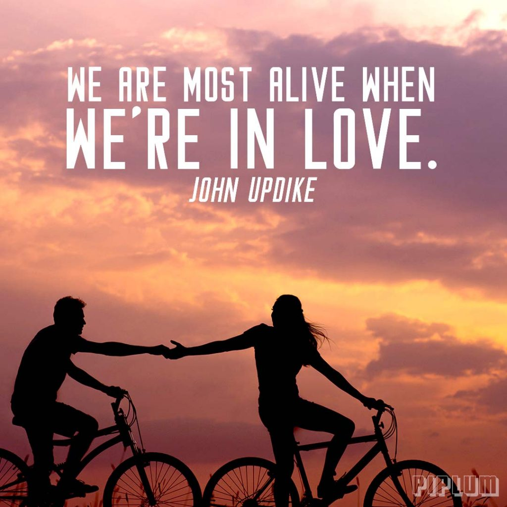 Love quote. Man and women holding hands while riding with bikes in the sunset.