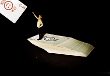 Motivational Quote. Man trying to pick a lucky card after many fails. surreal miniature photography.